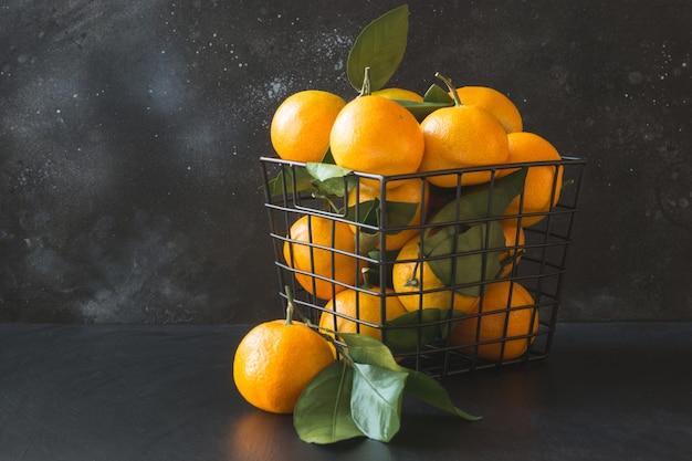 Fresh mandarins with leaves in modern bowl on black. healthy eating . copy space.