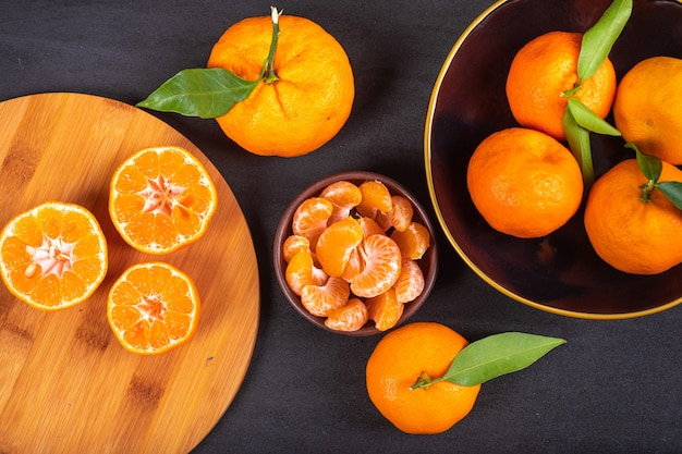 Fresh mandarins on wood cutting board and plate top view