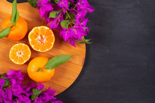 Fresh mandarins on wood cutting board with purple flowers on black surface with copy space