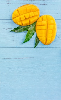 Fresh mango - beautiful chopped fruit with green leaves on bright blue timber background
