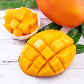 Fresh mango,beautiful chopped fruit with green leaves on bright wooden table background.