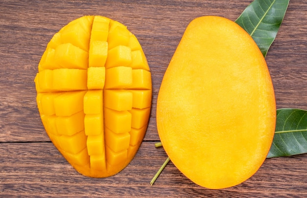Fresh mango - beautiful chopped fruit with green leaves on dark wooden timber background