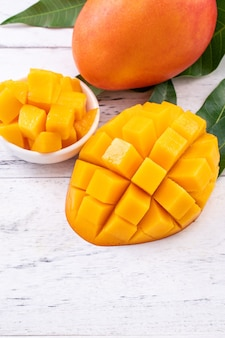 Свежее манго, красивые нарезанные фрукты с зелеными листьями на ярком фоне деревянного стола. концепция дизайна тропических фруктов, крупным планом, копией пространства.
