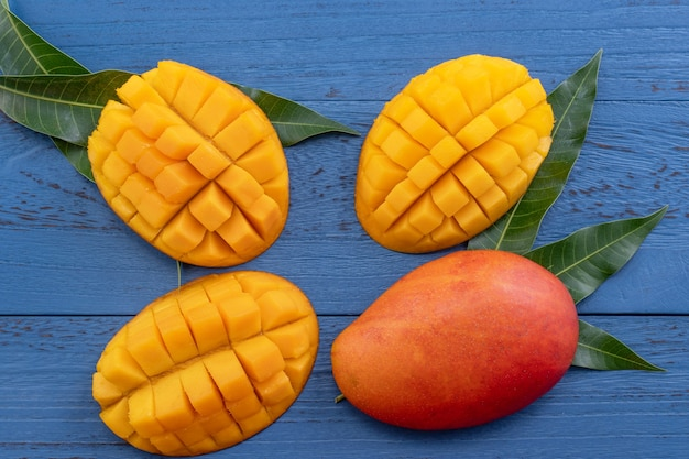 新鮮なマンゴー、暗い木製のテーブルの背景に緑の葉と美しいみじん切りの果物。トロピカルフルーツのデザインコンセプト。フラットレイ。上面図。コピースペース