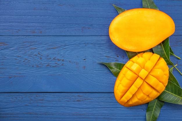 Свежее манго - красивый измельченный фрукт с зелеными листьями. концепция дизайна тропических фруктов. плоская планировка. вид сверху.