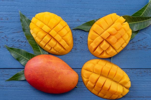 新鮮なマンゴー-緑の葉と美しいみじん切りの果物。トロピカルフルーツのデザインコンセプト。フラットレイ。上面図。