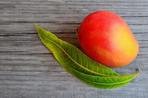 Fresh mango fruit and mango tree leaves on wood