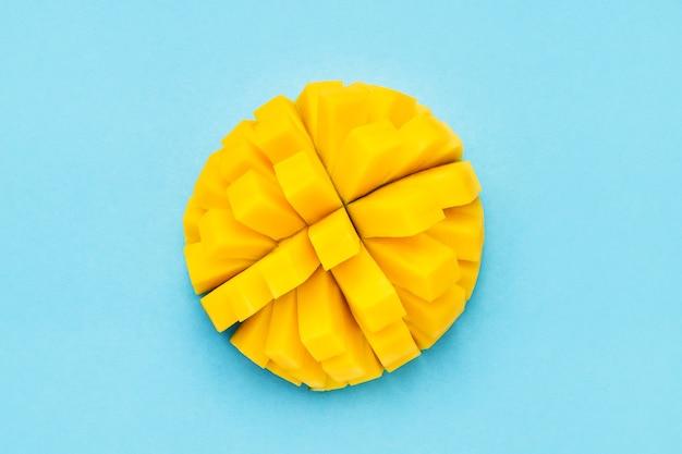 Свежие плоды манго с нарезанными кубиками кусками манго на голубом фоне. вид сверху, копировать пространство