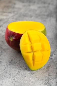 Fresh mango fruit with slices placed on stone background.