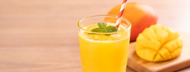 Fresh mango juice with beautiful chopped pulp flesh on bright wooden table background
