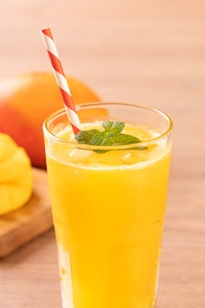 Fresh mango juice with beautiful chopped pulp flesh and straw on bright wooden table background
