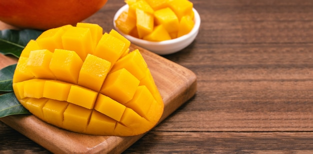Fresh mango - juicy chopped mango cubes on wooden cutting board and rustic timber background
