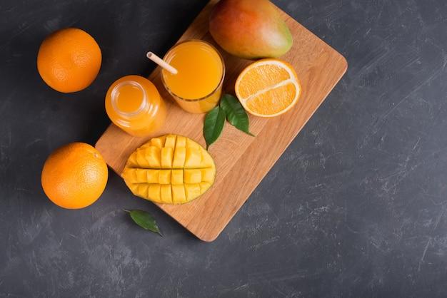 Fresh mango orange juice with ripe mangoes and orange fruit on wooden board