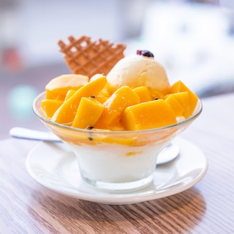 Fresh mango shaved ice with a scoop of ice cream and juice sauce in summer restaurant, lifestyle, popular food in taiwan, close up