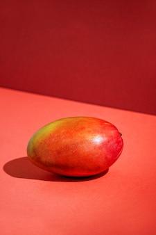 新鮮なマンゴー、日光の下でテーブルの背景、現代の静物、赤い背景、過酷な光