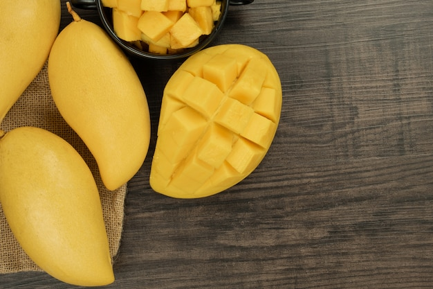 Fresh mango top view. wooden background and copy space for add text.