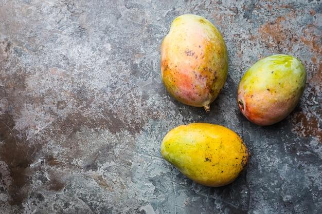 コピースペースでグレーの上に新鮮なマンゴートロピカルフルーツ。