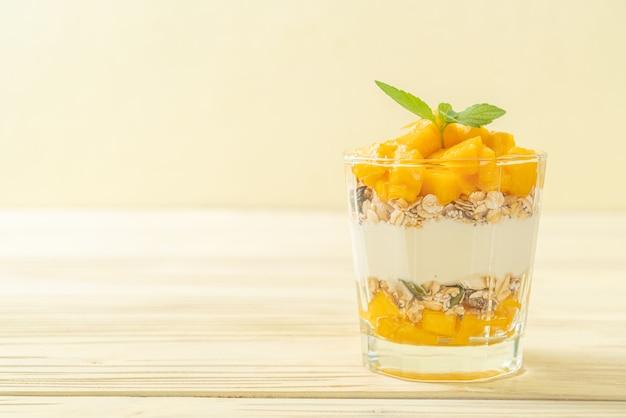 Fresh mango yogurt with granola in glass - healthy food style