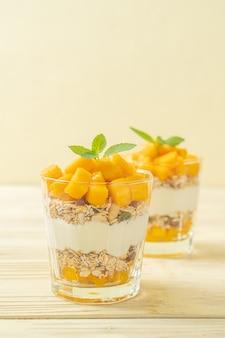 Йогурт из свежего манго с гранолой в стакане - стиль здорового питания