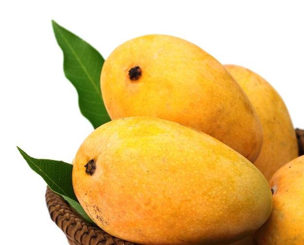 Свежие манго с зелеными листьями на корзине