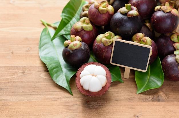 タイのフルーツの女王のための黒板と木のテーブルの上に新鮮なマンゴスチン果物