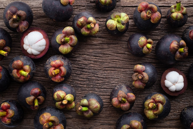 Fresh mangosteen fruit with frame on wood table.