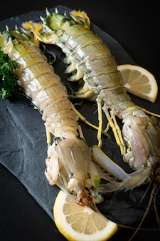 Fresh mantis shrimp with lemon on black board