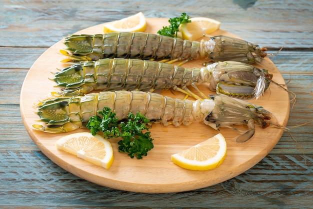 Fresh mantis shrimp with lemon on wood board