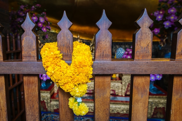 A fresh marigold garland hanging on the wooden fence in wat pho temple, bangkok, thailand.