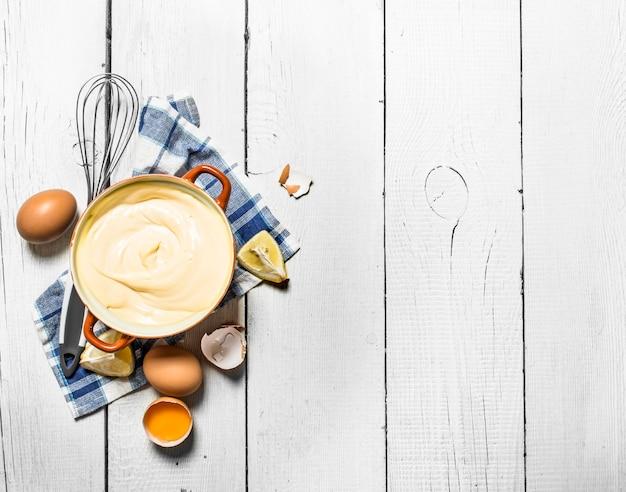 Свежий майонез с ингредиентами на белом деревянном фоне