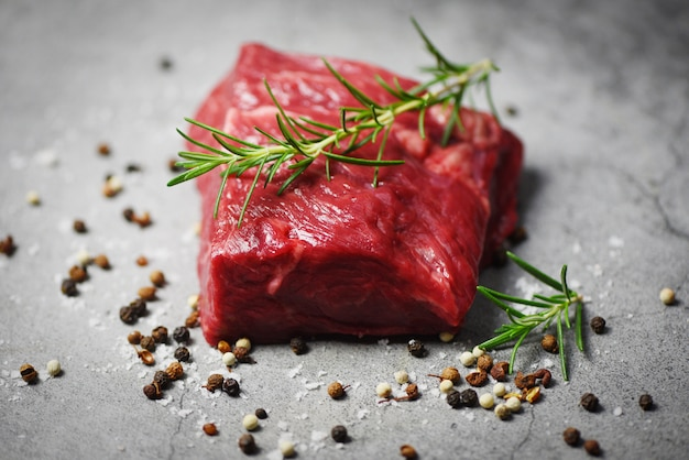 Fresh meat beef sliced on black background - raw beef steak with herb and spices and rosemary