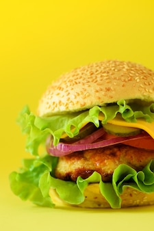 Fresh meat burgers on yellow background. take away meal. fast food concept. unhealthy diet with copy space