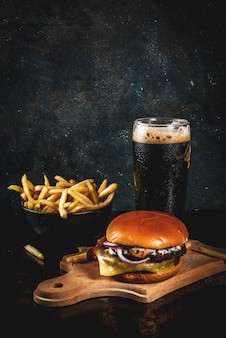 Fresh meat and cheese burger with french fries and glass of dark ginger beer, on dark blue ,