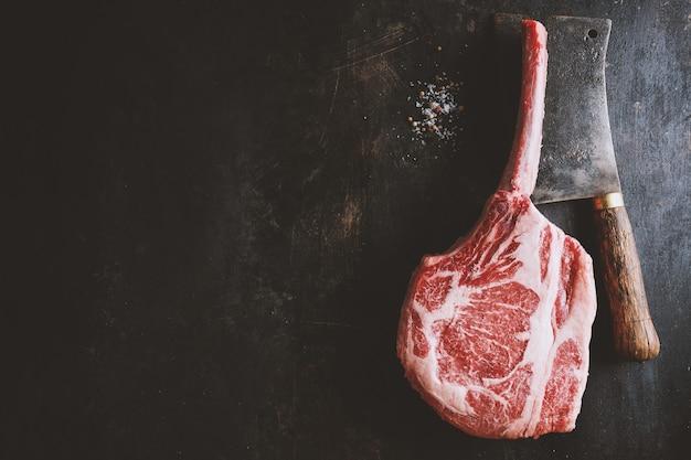 오래 된 나무 보드에 신선한 고기 토마 호크 스테이크입니다. 어두운 배경입니다. 확대