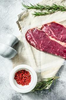 Свежее мясо, мраморная говядина в вакуумной упаковке, стейк из нью-йорка. темная стена. упаковка из супермаркета.