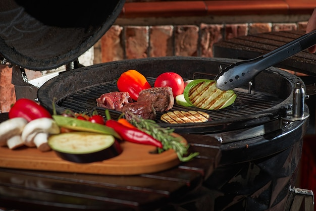 Fresh meat and vegetables grilled at a homemade weekend barbecue. cooking concept, dark kitchen.