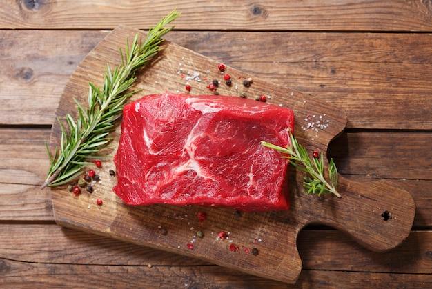 Свежее мясо с ингредиентами для приготовления на деревянной доске, вид сверху