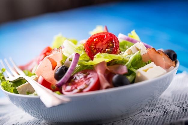 Свежий средиземноморский салат с оливками, помидорами, пармезаном и ветчиной прошутто