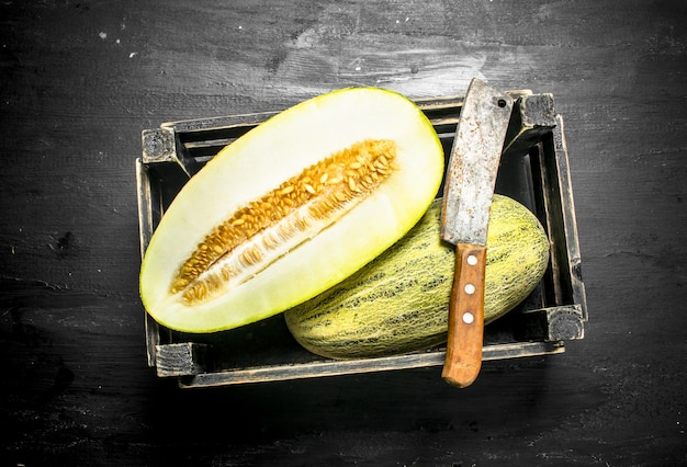 Fresh melon in a box with a hatchet on the black chalkboard