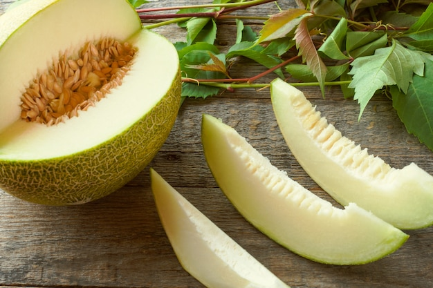 Fresh melon cut into pieces on a wooden table