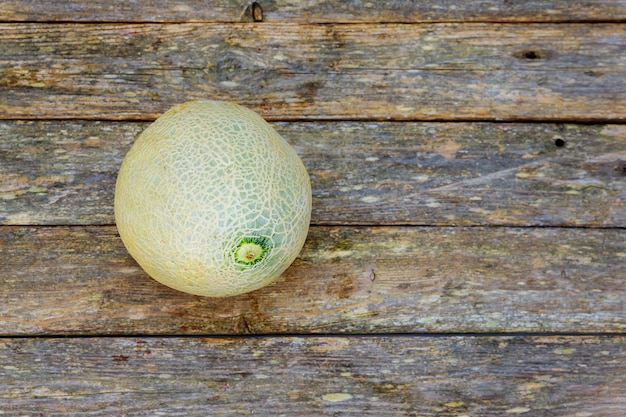 Fresh melons on old wooden background.