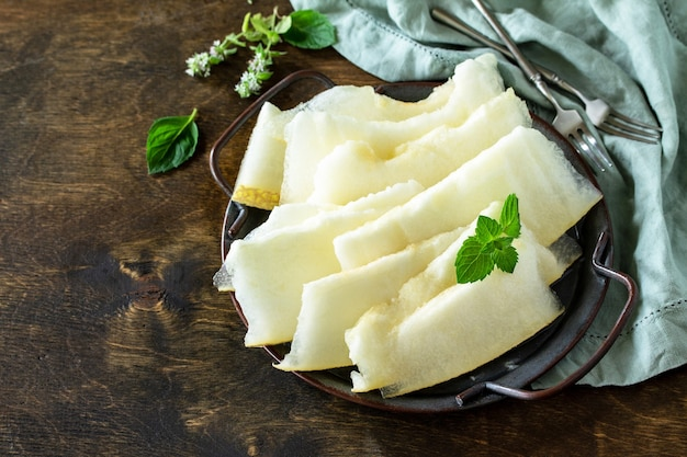 Fresh melons sliced to pieces on rustic wooden table free space for your text