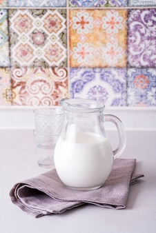 Fresh milk in glass jug and glass, wall with old colored kitchen tiles