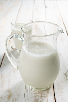 Fresh milk in glass jug and glass on wood