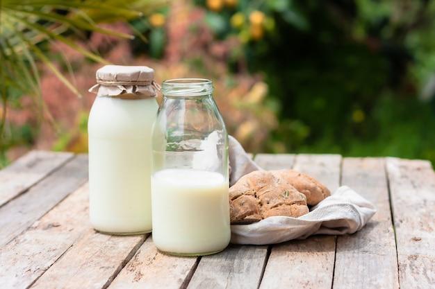 自然の背景に素朴な木製のテーブルにボトルと丸い茶色のライ麦フラットブレッドの新鮮な牛乳。