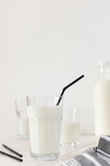 검은 빨대가 있는 안경에 신선한 우유, 맛있는 건강 음료