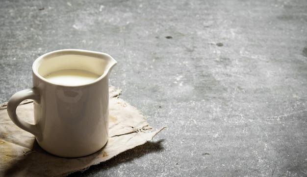 石のテーブルのマグカップに新鮮なミルク