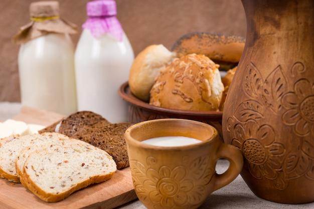 Свежее молоко в керамической кружке в деревенском стиле подается с нарезанным цельнозерновым хлебом для здоровой закуски