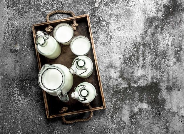 古い箱に入った新鮮な牛乳。素朴な背景に。