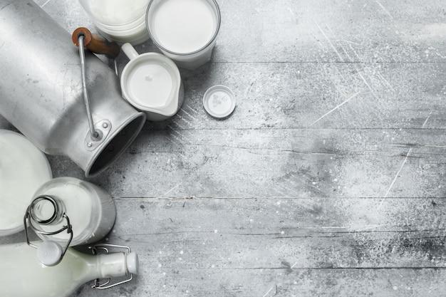 Свежее молоко в стаканах, бутылках и кувшине. на деревенской поверхности.